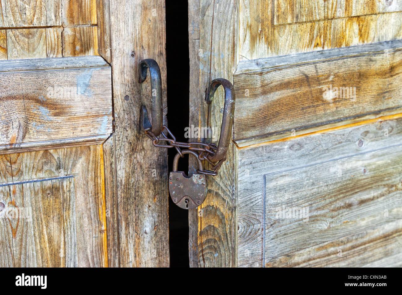 Rusty padlock on an old wooden door - Stock Image