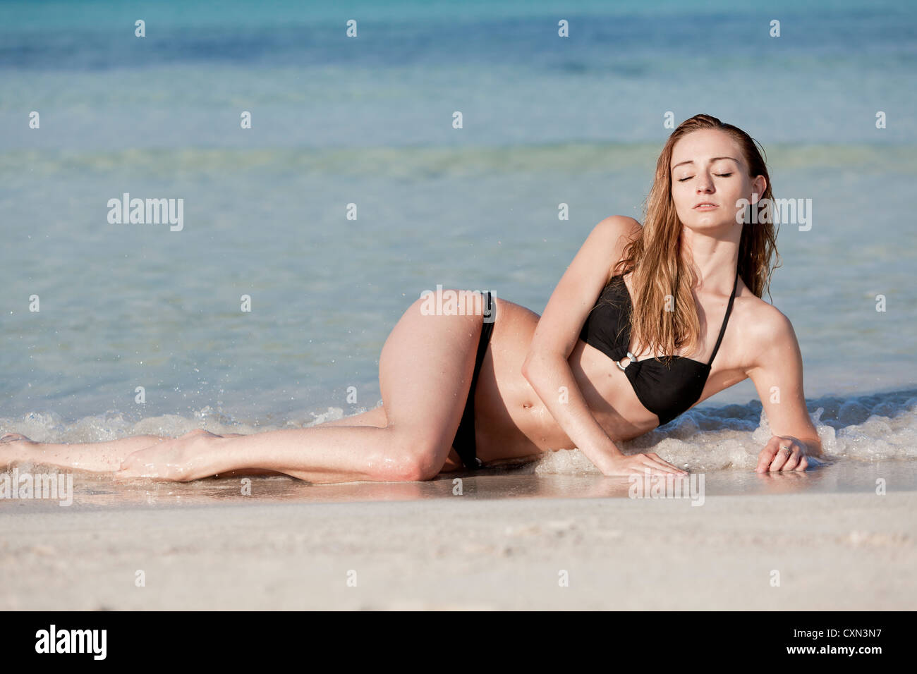 8f1254a44da57 Young woman with black bikini Sexy girls on the beach in water with blue  sky in summer vacation