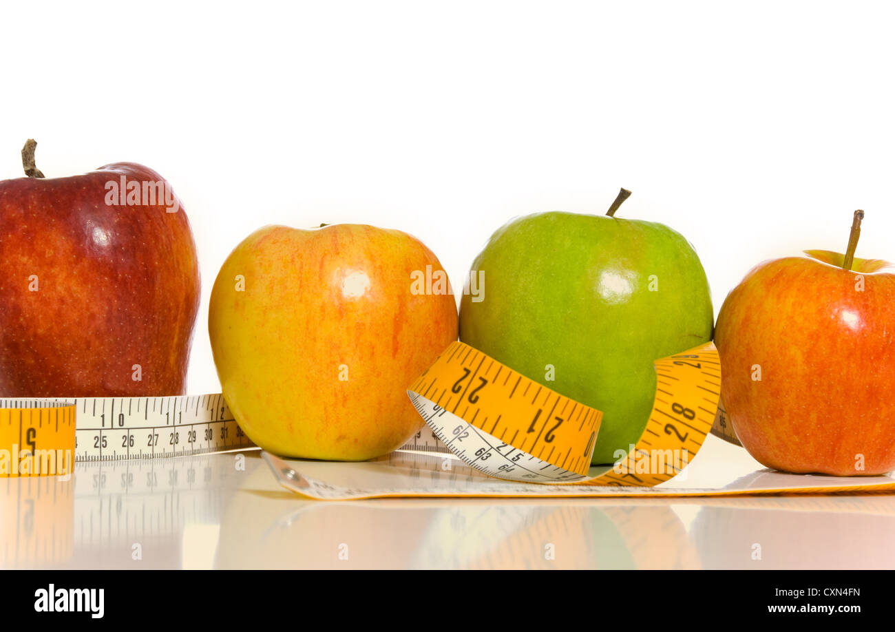 A variety of apples and a tape measure on white background, symbol of healthy living or dieting - Stock Image