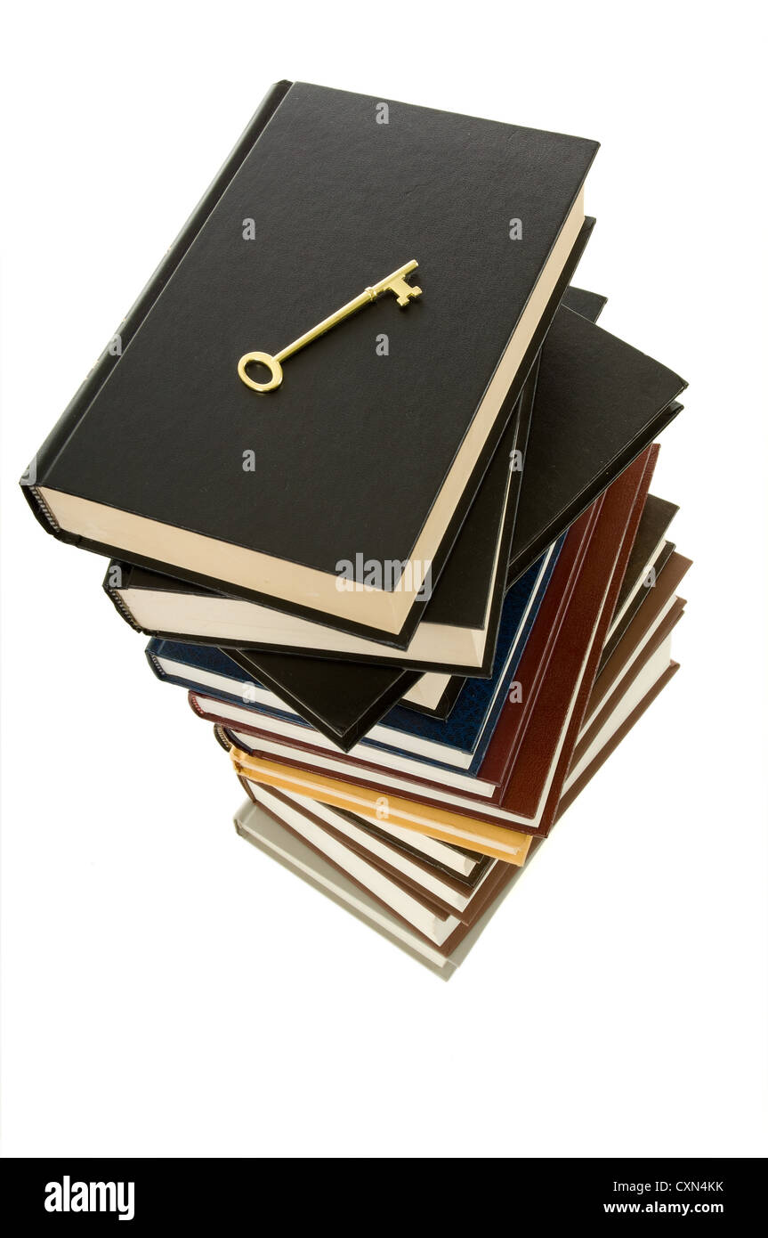 Huge stack of books with a skeleton key on top to signify the key to knowledge can be found in books Stock Photo
