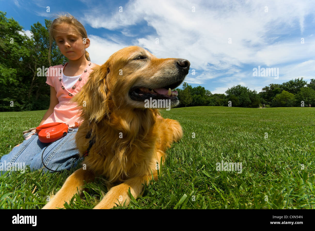 Young girl at park with pet Dog Stock Photo