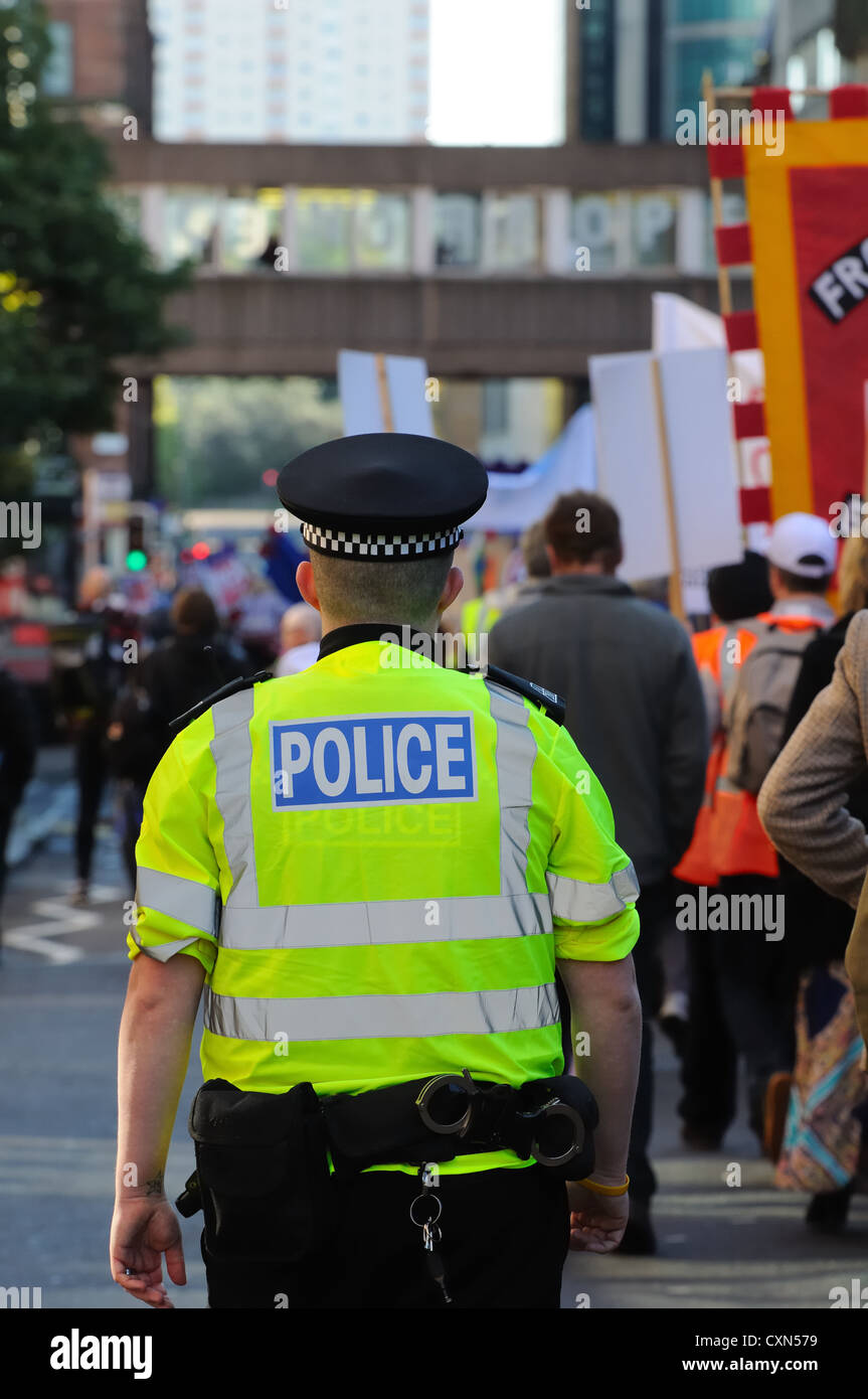 Policeman walking beside demonstration march. - Stock Image