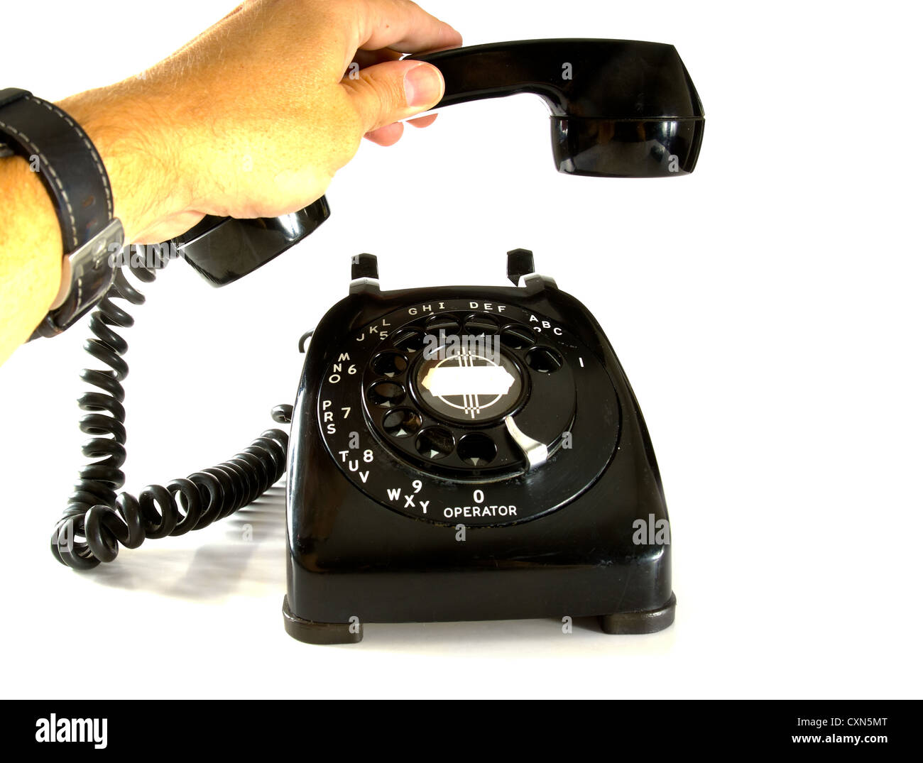 Man's hand picking up the receiver on a 1950's vintage telephone - Stock Image