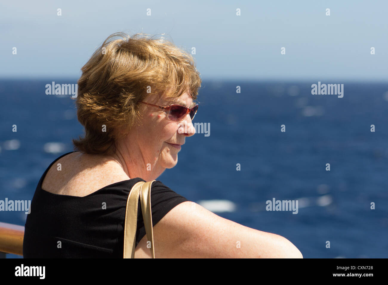 woman enjoying seaview from the rails of the cunard liner 'Queen Victoria' - Stock Image