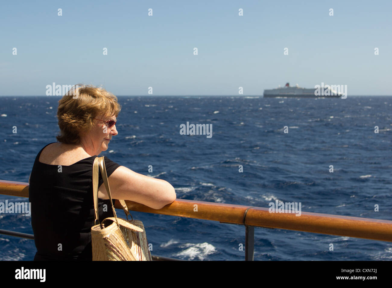 woman enjoying seaview from the rails of the Cunard liner 'Queen Victoria' looking across at sister ship - Stock Image