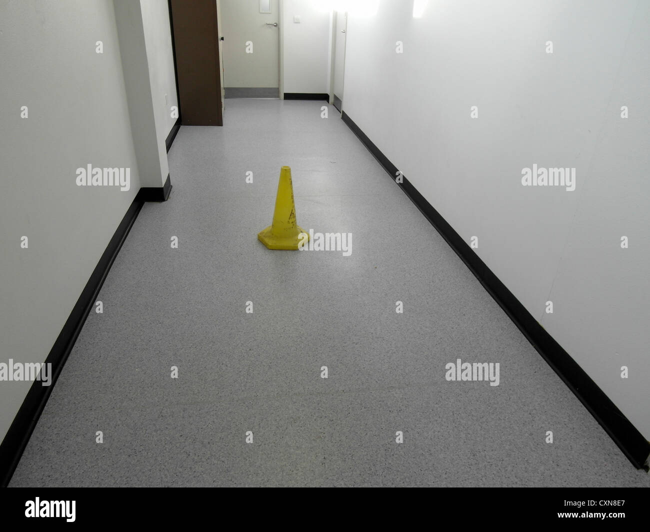 Yellow warning cone on the floor in a corridor. - Stock Image
