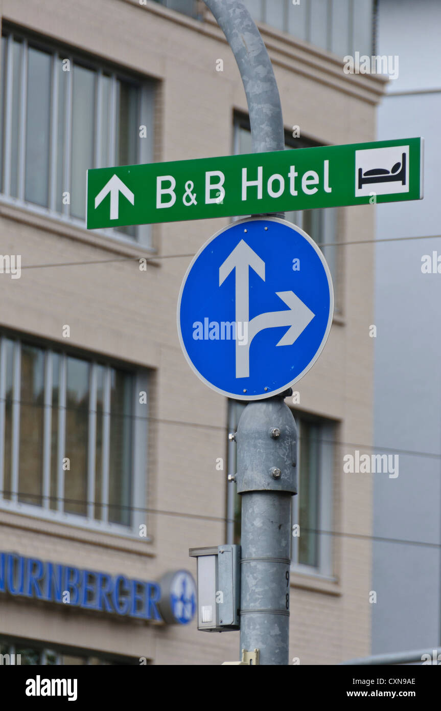 """B&B Bed and Breakfast hotel sign and regulatory road sign """"go straight or right"""", signage - Stock Image"""