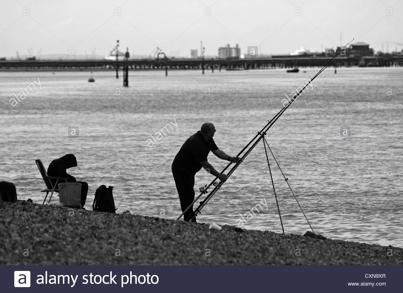 Black & White landscape image - son fishing with his father on The Solent Southampton UK on a May afternoon - Stock Image