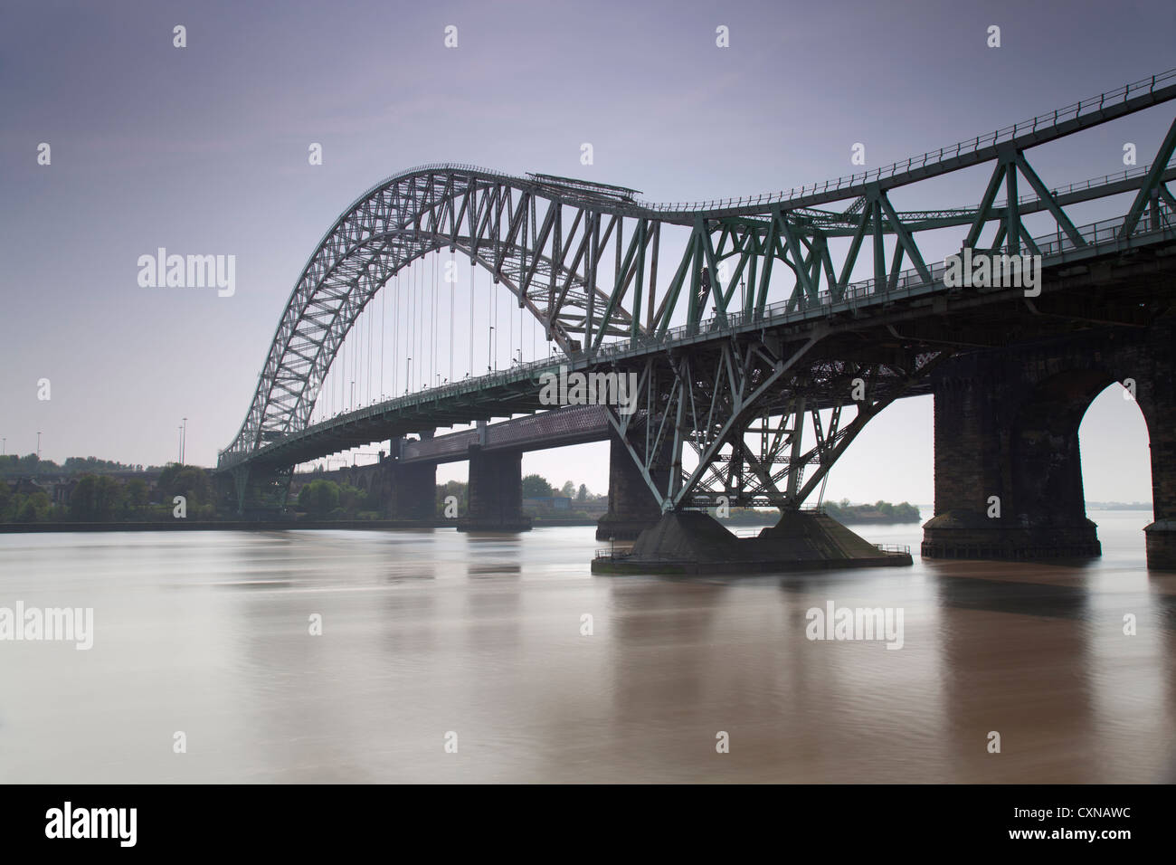 Long exposure day time image of the Runcorn Widnes bridge which spans the river Mersey and Manchester ship canal. - Stock Image