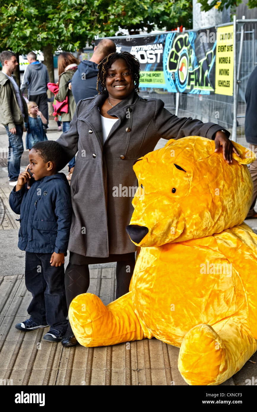 Lucky prizewinner with her giant teddy bear  prize at Nottingham's  historic Goose Fair. - Stock Image
