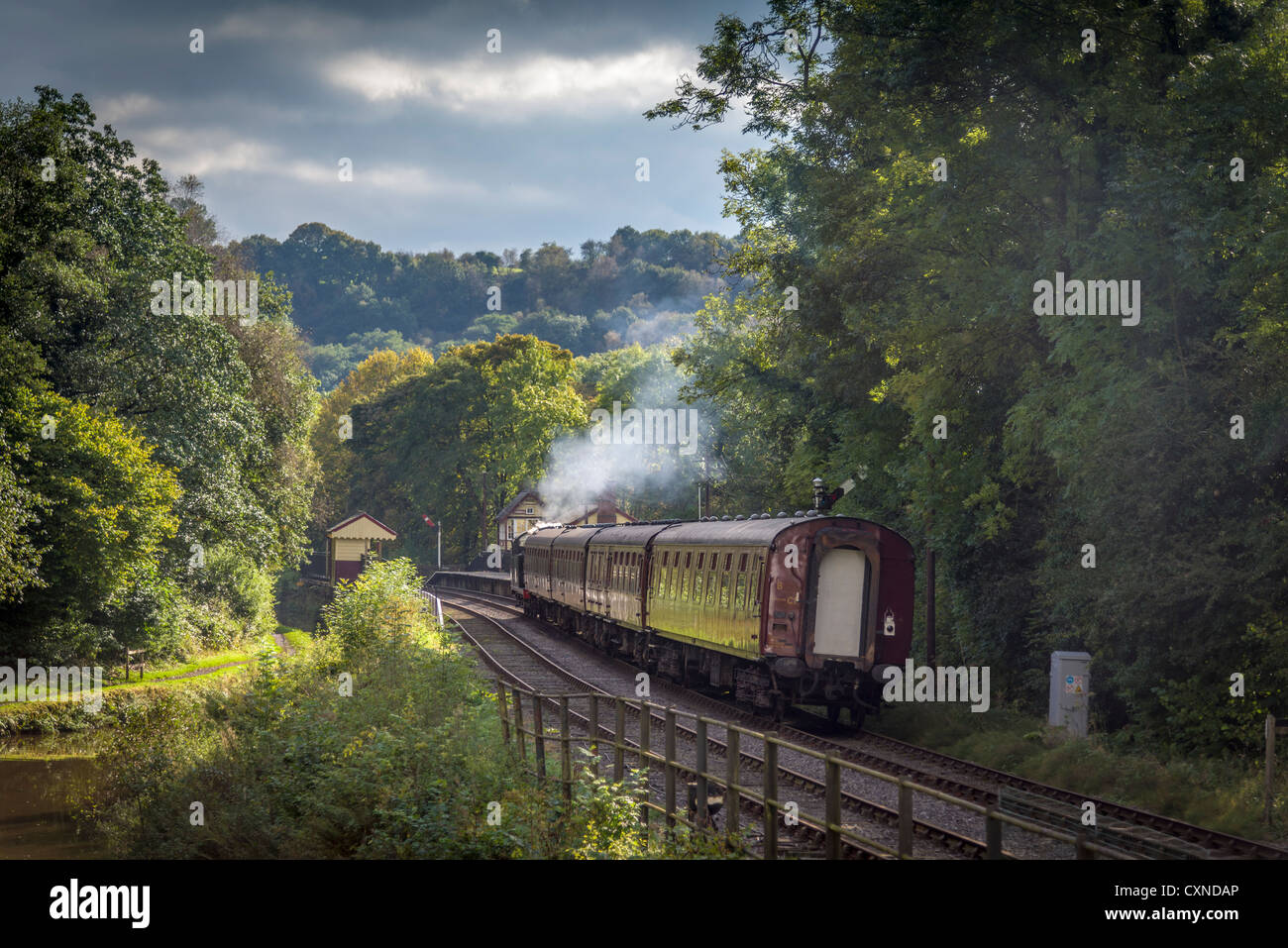 Consall station on the Churnet Valley Railway with a steam train passing by the Caldon canal in Staffordshire. - Stock Image