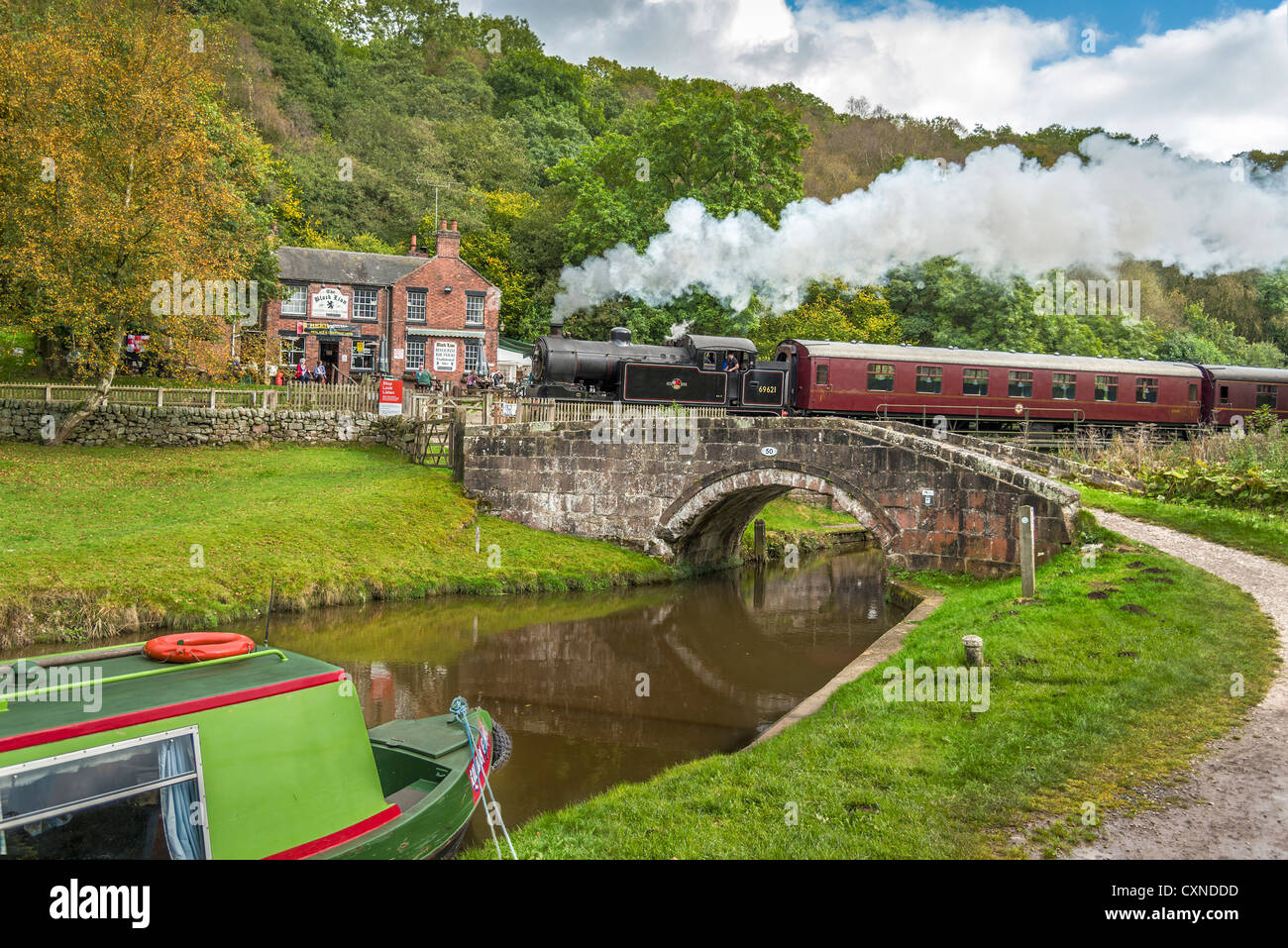 Black Lion pub Consall on the Churnet Valley Railway with a steam train passing by over the Caldon canal in Staffordshire. - Stock Image