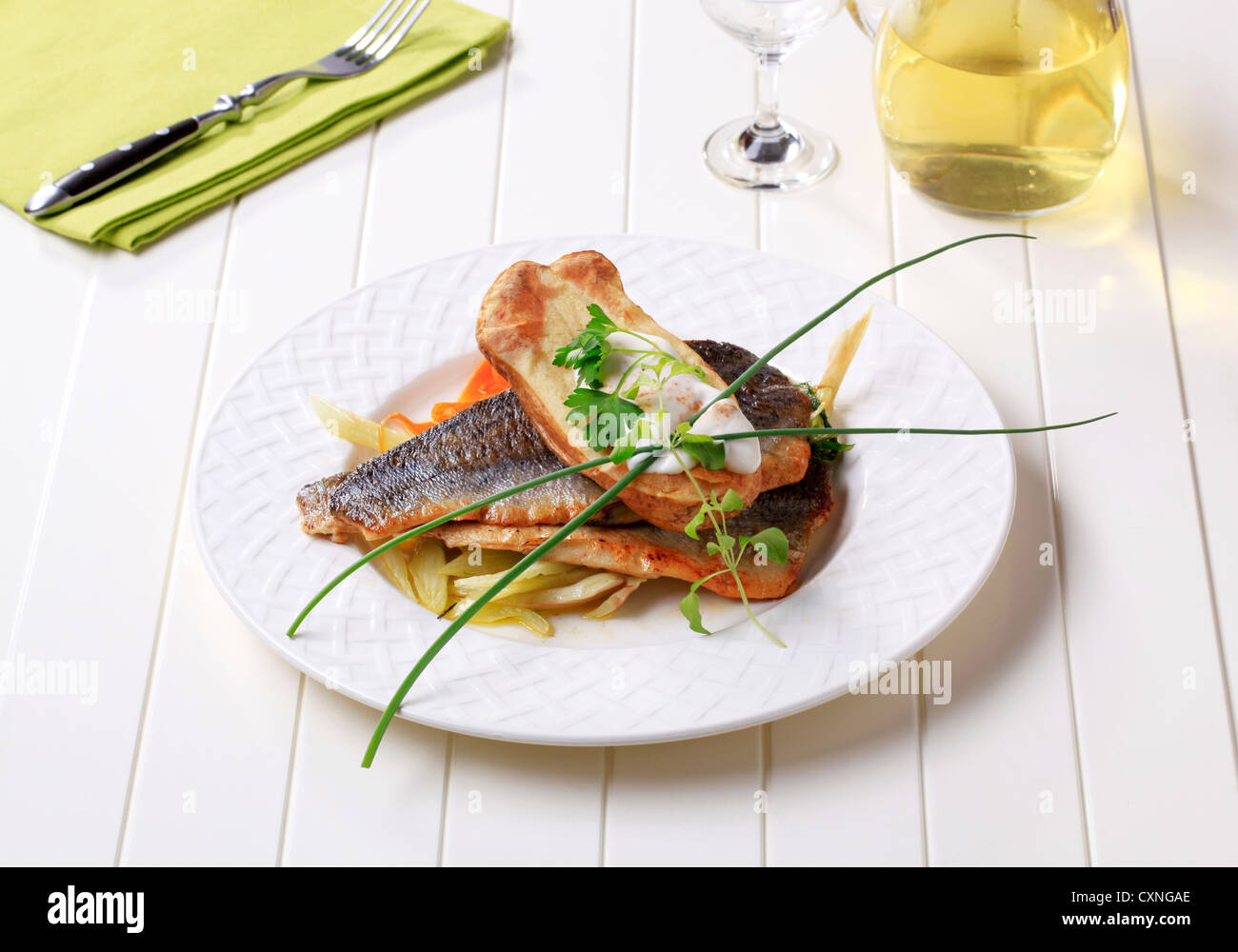 Pan fried fish fillets with baked potato and sauteed vegetable - Stock Image