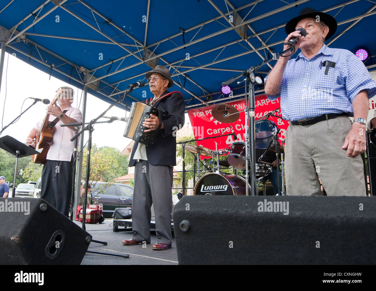 Tejano style music group including young white male, senior Mexican-Americans and female Hispanic play at a church - Stock Image