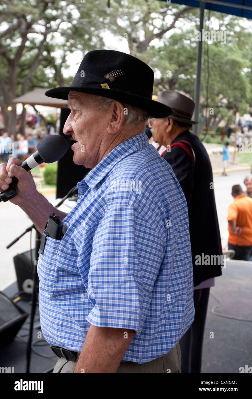 Mexican-American senior sings with a Tejano style music group at a church festival in Austin, Texas - Stock Image