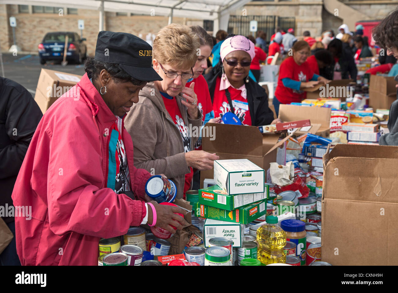 Volunteers Sort and Pack Food Donated for Food Banks and Soup Kitchens - Stock Image