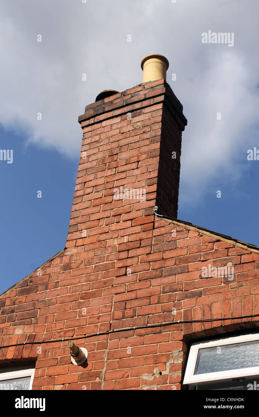 Chimney of old brick house or home with blue sky and cloudscape background. - Stock Image