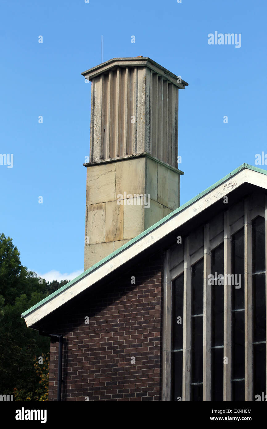 Chimney on modern crematorium building with blue sky background. - Stock Image