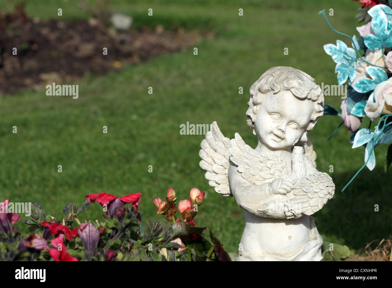 Memorial angel statue in cemetery next to blooming flowers. - Stock Image