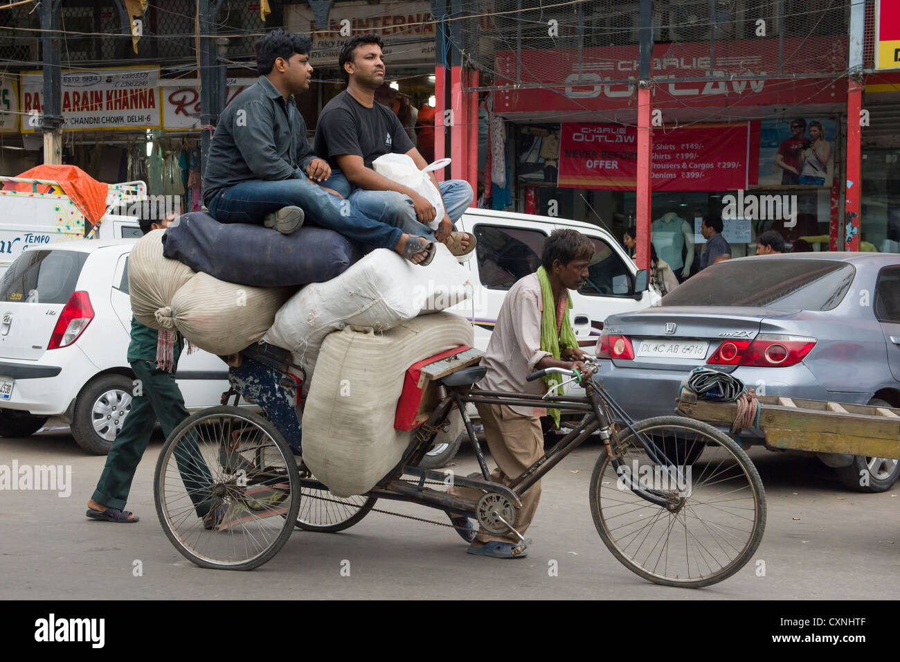 Two young affluent men sitting on top of sacks on an overloaded cycle rickshaw, Chandni Chowk, Old Delhi, India - Stock Image