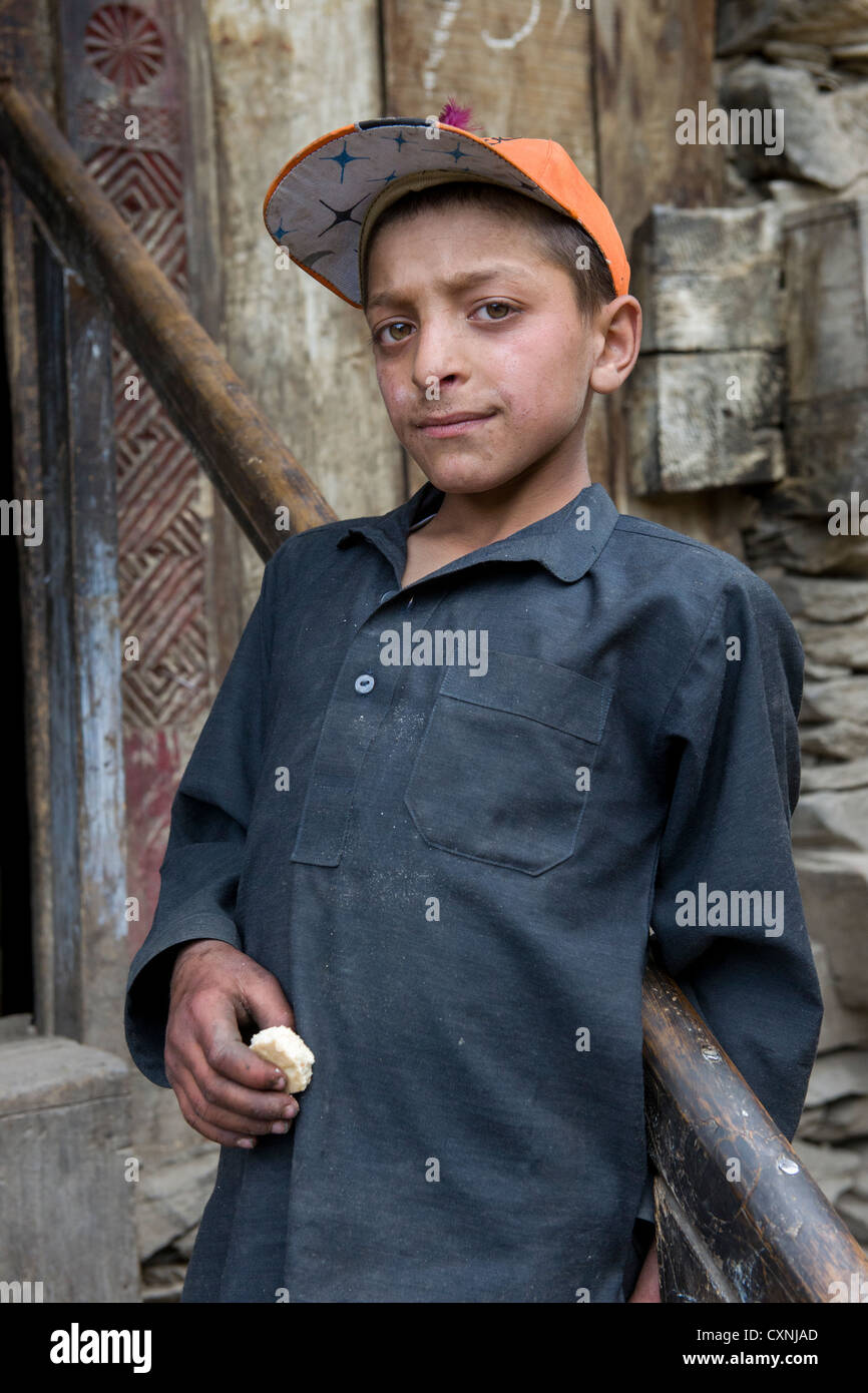 Kalash boy on the steps of a house at Krakl Village, Bumburet Valley, Chitral, Khyber-Pakhtunkhwa, Pakistan - Stock Image