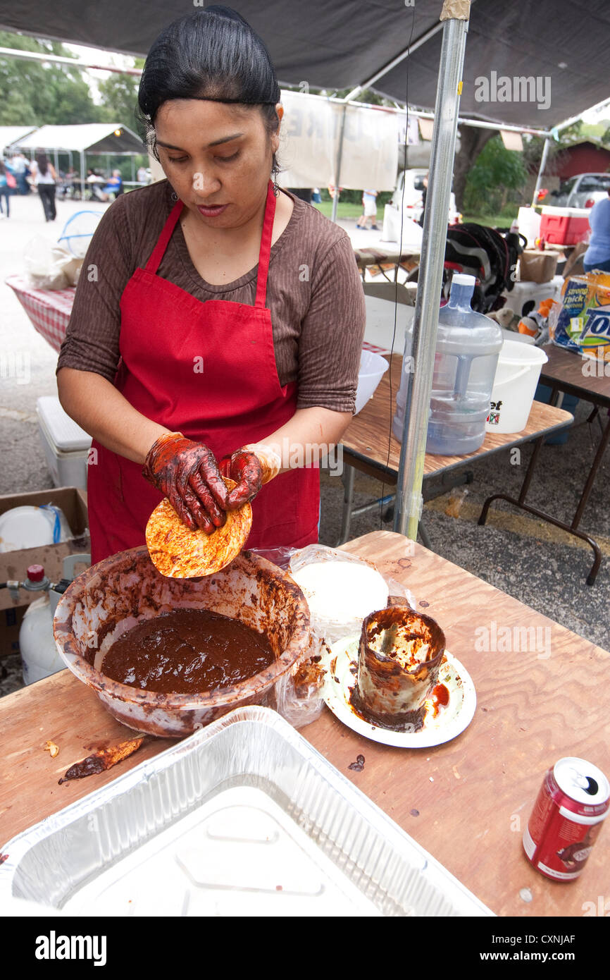 Hispanic woman prepares traditional Mexican enchiladas by covering corn tortilla with red chile sauce at outdoor Stock Photo
