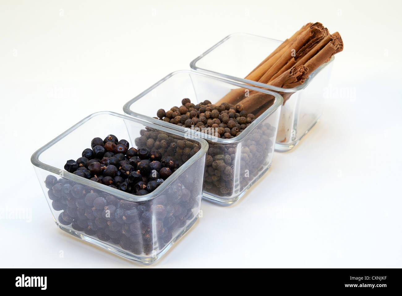cinnamon, allspice grains / pimento and Juniper berries in a glass bowl Stock Photo