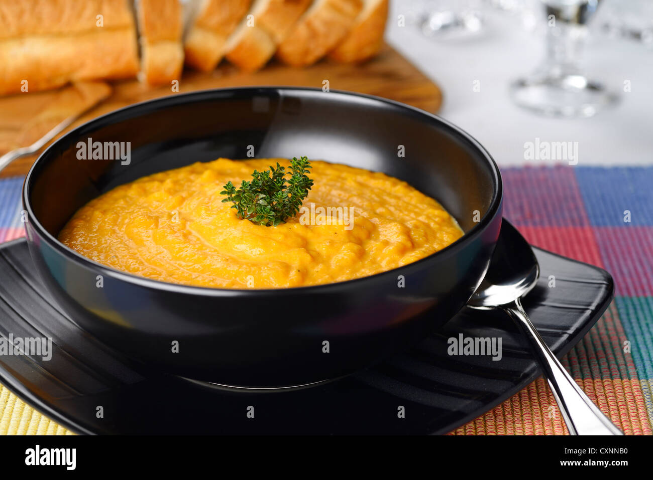 Cream carrot tomato orange soup with thyme garnish in black bowl with sliced bread - Stock Image