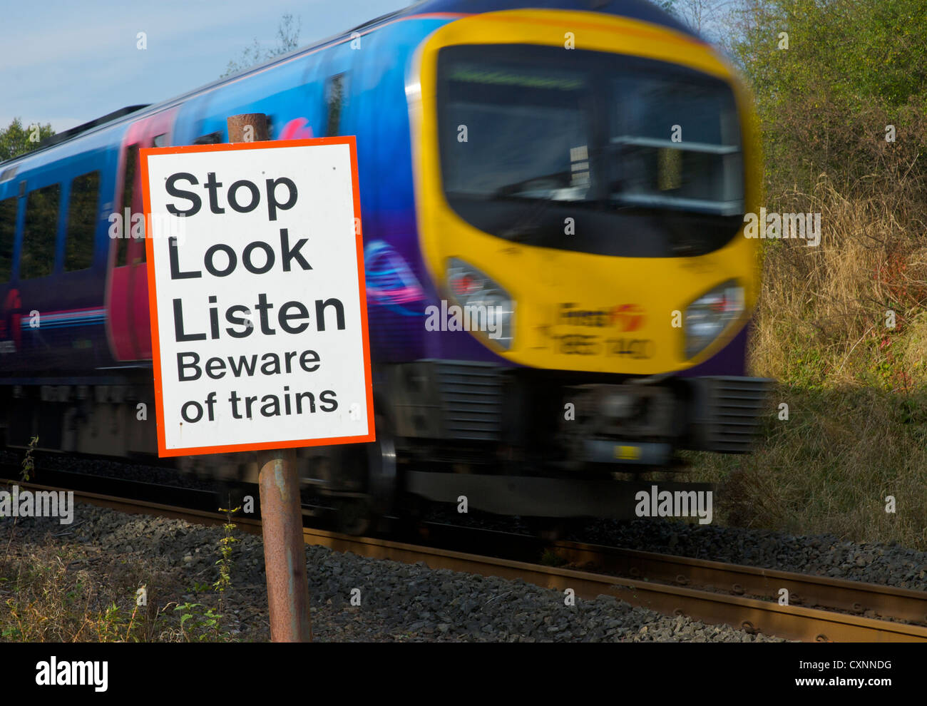 Speeding train and sign, by pedestrian crossing over railway line, warning people about trains - Stock Image