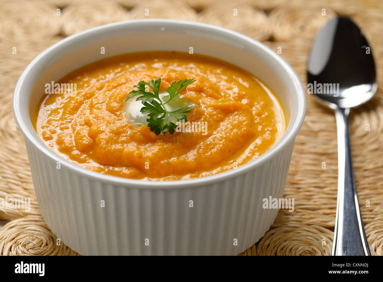 Carrot soup with cream and parsley in white bowl on woven grass placemat and spoon - Stock Image