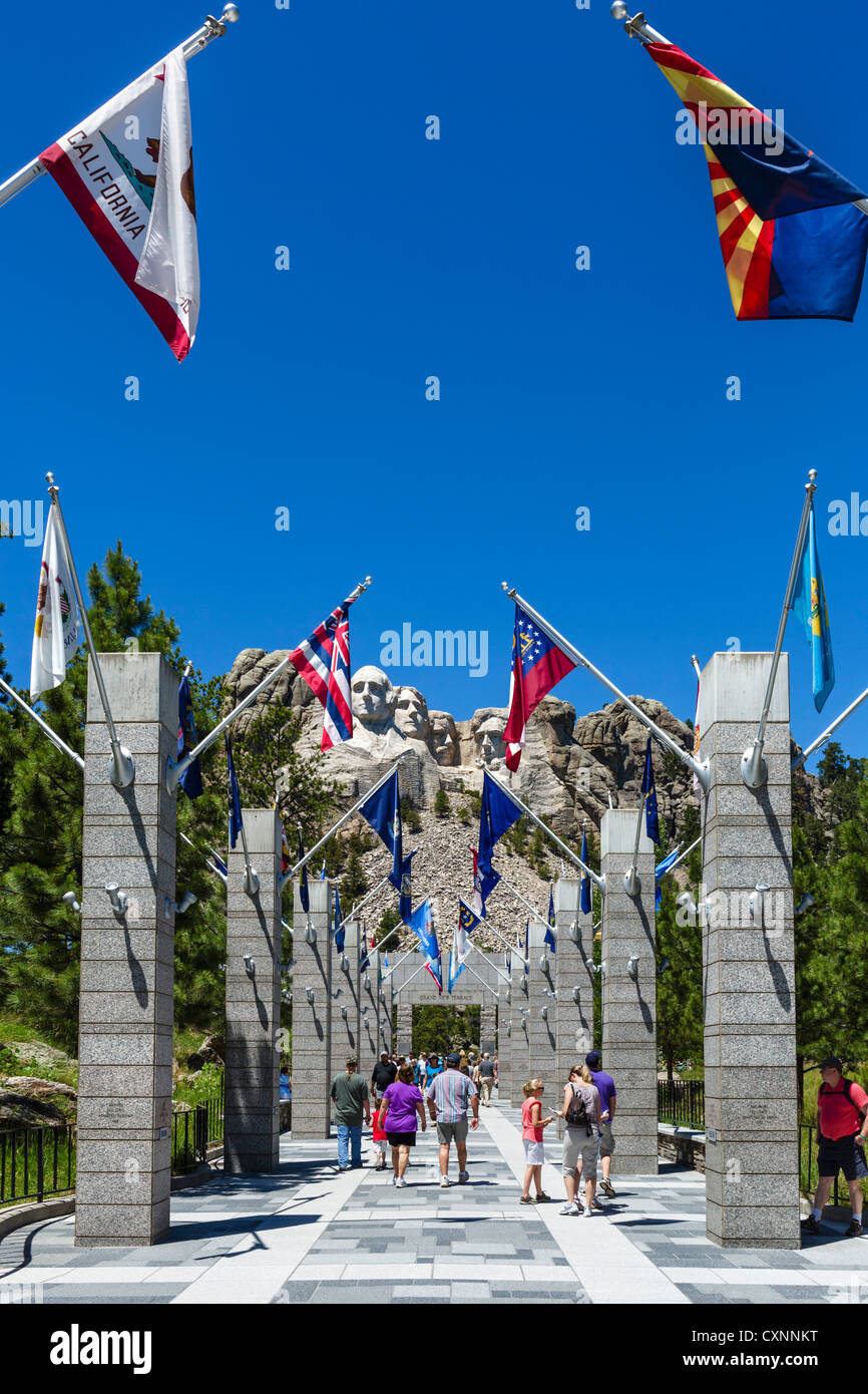 Tourists at Mount Rushmore National Memorial with avenue of state flags leading to viewing area, Black Hills, South Stock Photo