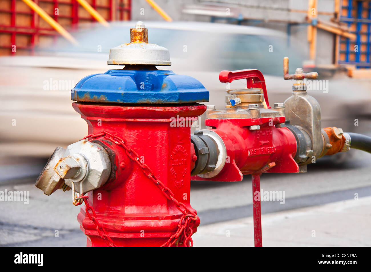 Red fire plug with a lot of other devices and handles isolated by a white car in movement Stock Photo
