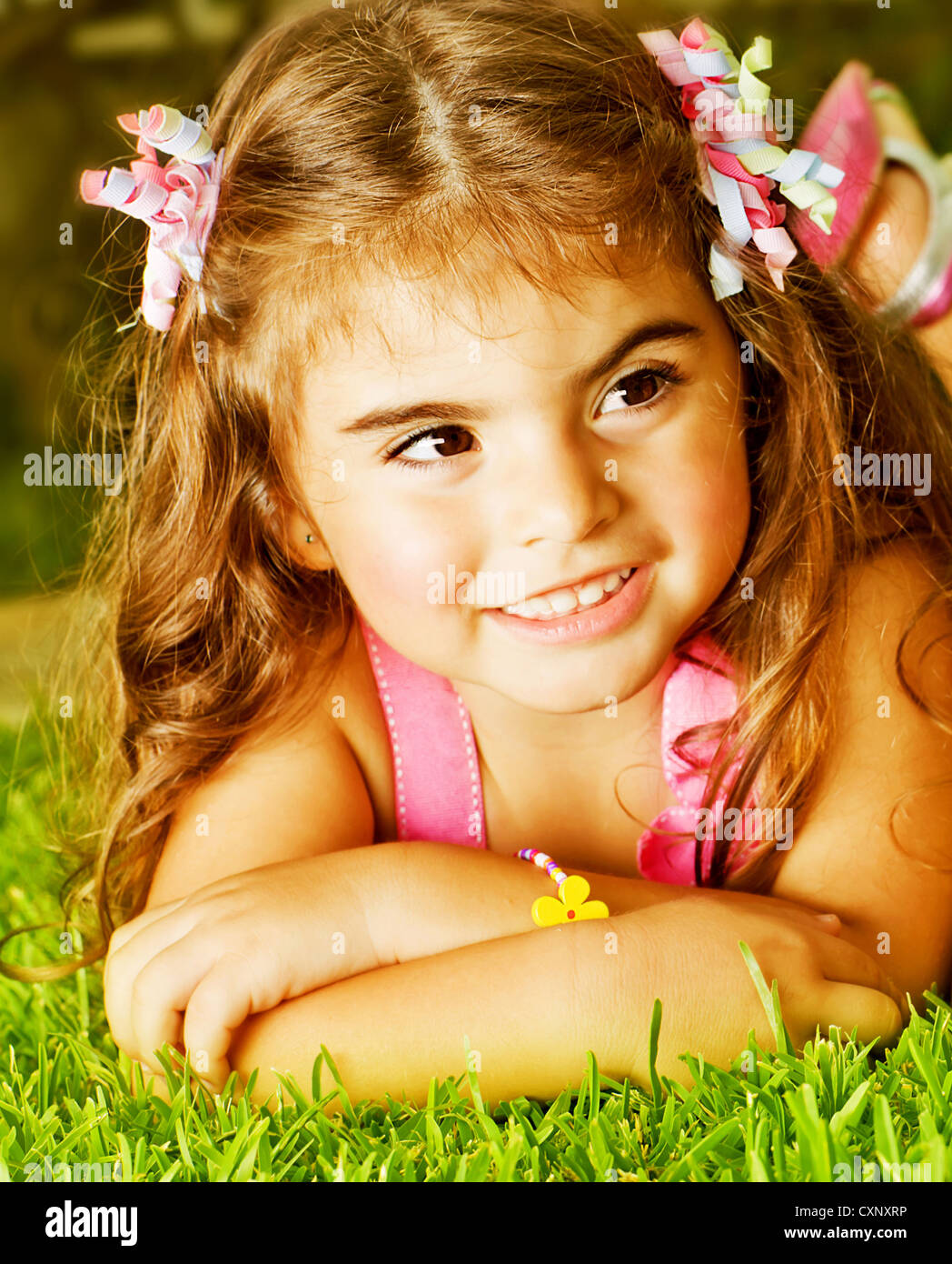 photo of cute little girl lying down fresh green grass, adorable