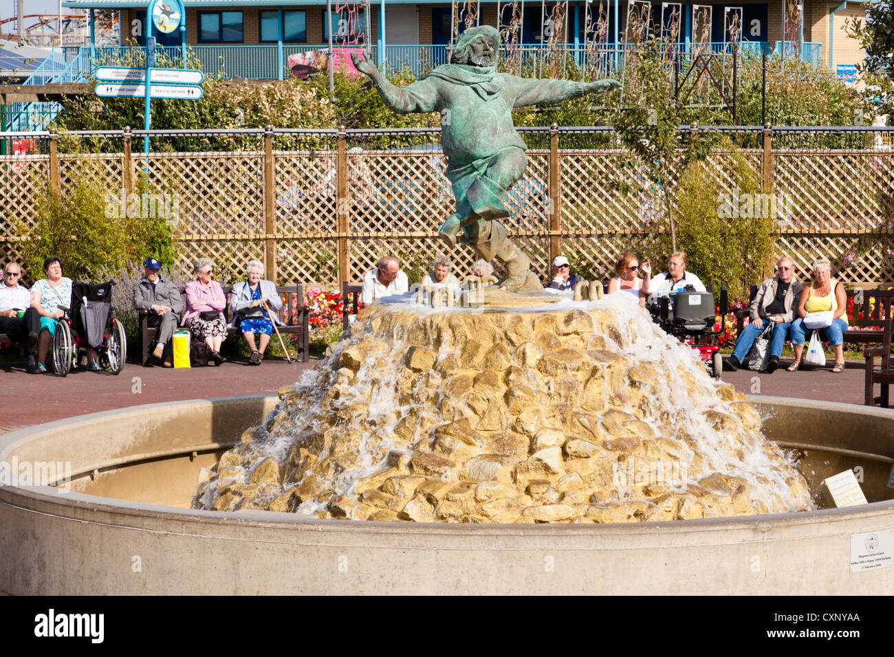People on holiday sitting around the Jolly Fisherman sculpture in Skegness, Lincolnshire, England, UK - Stock Image