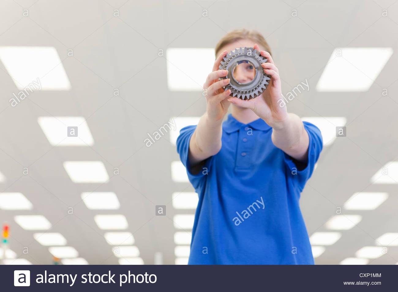 Portrait of smiling engineer peering through gear wheel - Stock Image
