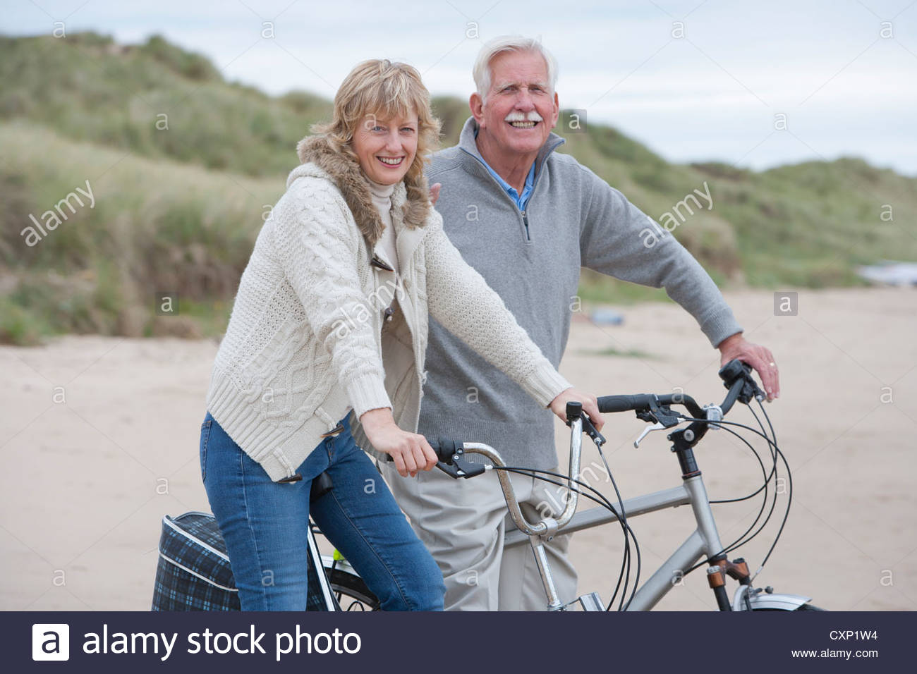mature couple riding cycles on winter beach holiday stock photo
