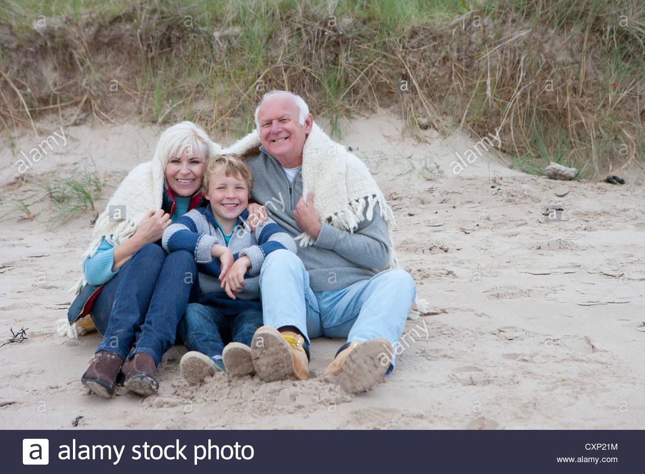Grandparents And Grandson Sheltering Under Blanket On Beach - Stock Image