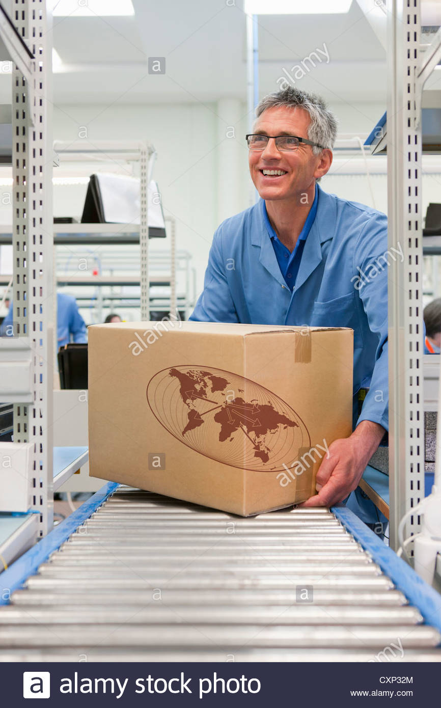 Smiling worker placing cardboard box on conveyor belt in factory - Stock Image