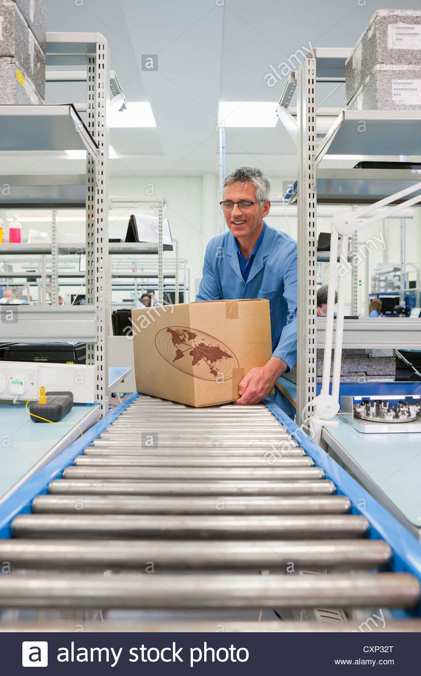 Worker placing cardboard box on conveyor belt in factory - Stock Image