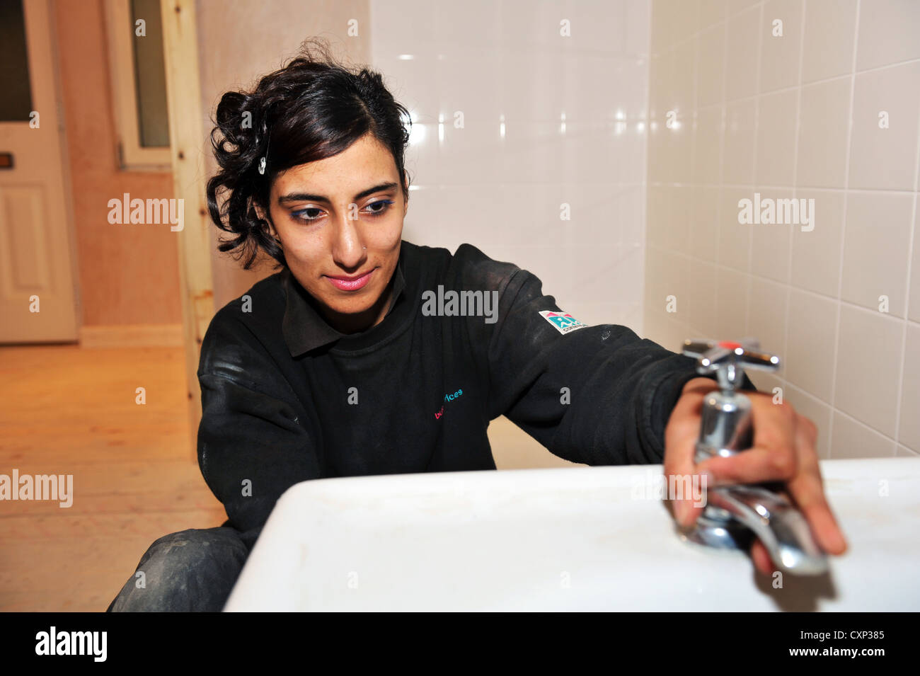 A Young Plumbing Apprentice practices at a training centre in Bradford - Stock Image