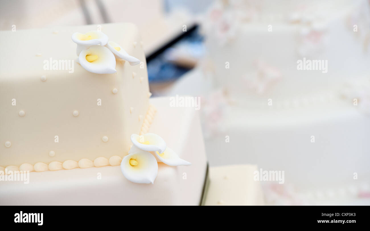 Close up of flowers made of icing sugar on a tiered wedding cake. - Stock Image