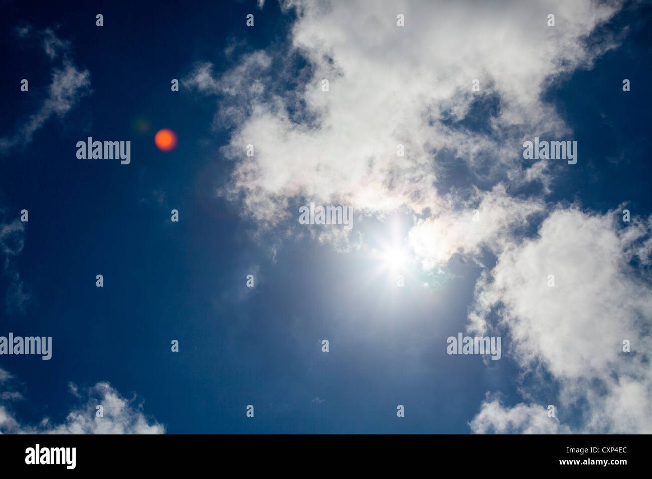 sun and light wispy cloud with blue sky with lens flare - Stock Image