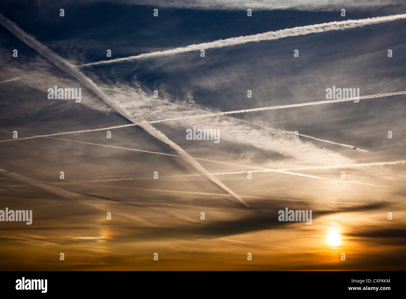 Aircraft vapour trails cover the sky's over west London on an early Autumn evening. - Stock Image