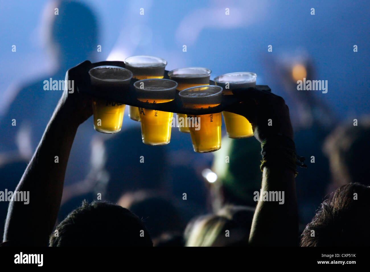 Ambiance during live rock concert and man bringing pints of beer in plastic cups to friends among spectators / crowd, - Stock Image