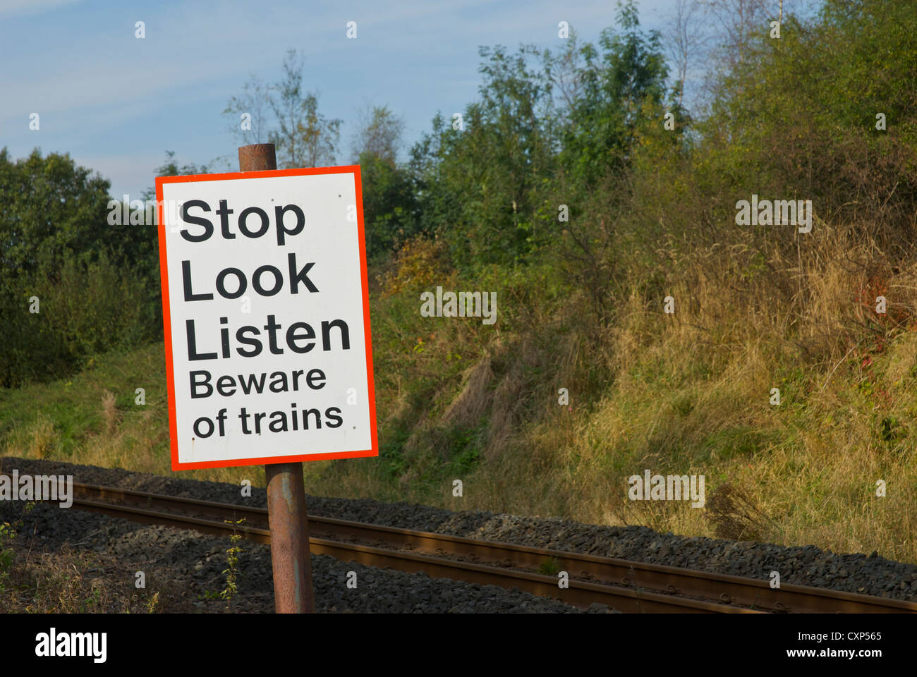 Sign by pedestrian crossing over railway line, warning people about trains - Stock Image