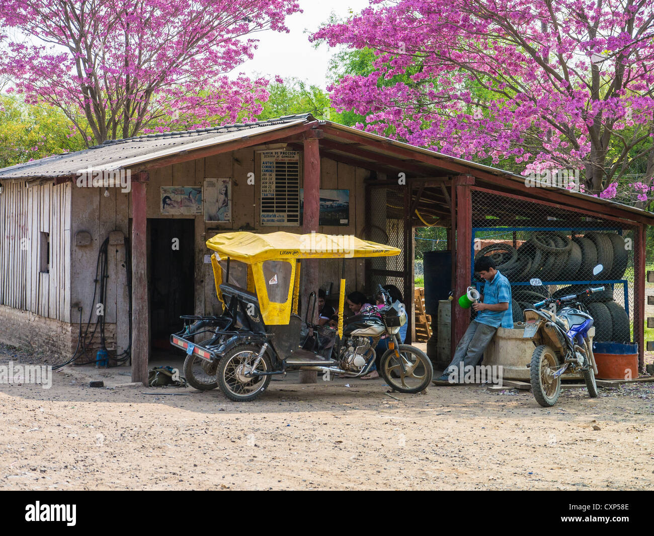 A man sits next to his motorcycle pedicab in front of a modest house in the Chaco region of Paraguay. - Stock Image
