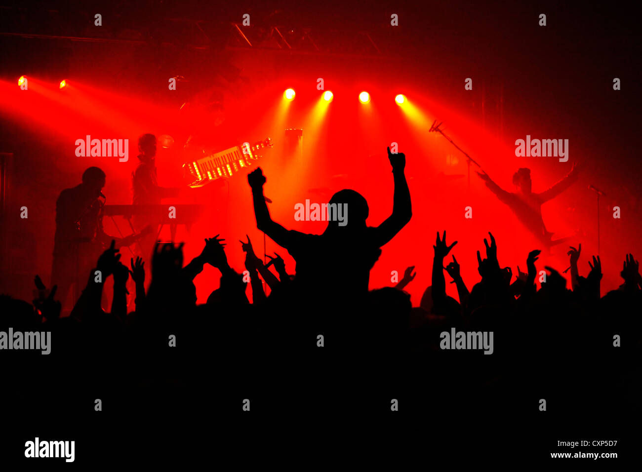 Silhouetted spectators / crowd and ambiance during live rock concert with rockers on stage illuminated by red spotlights - Stock Image