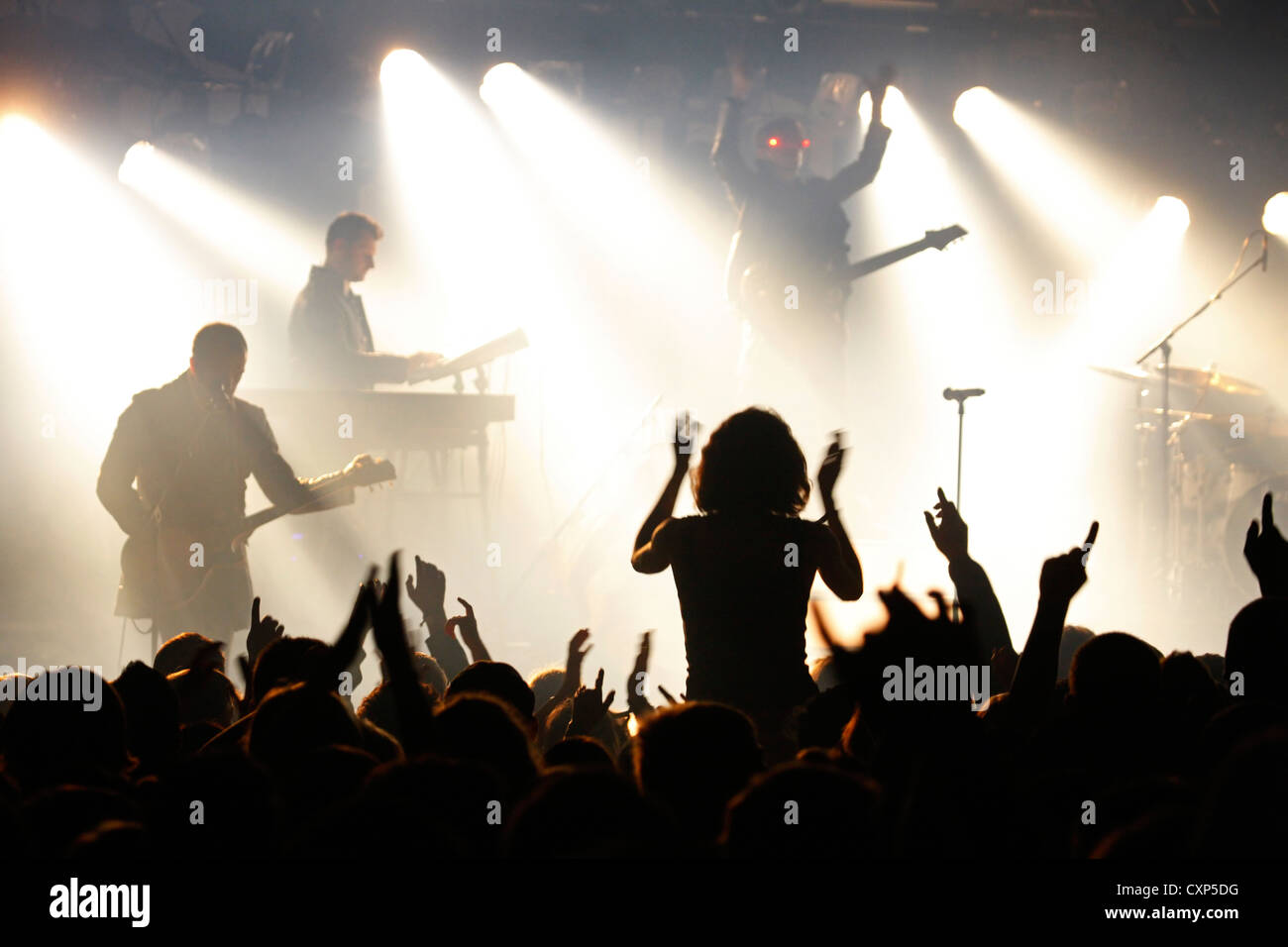 Silhouetted spectators / crowd and ambiance during live rock concert with rockers on stage illuminated by spotlights - Stock Image