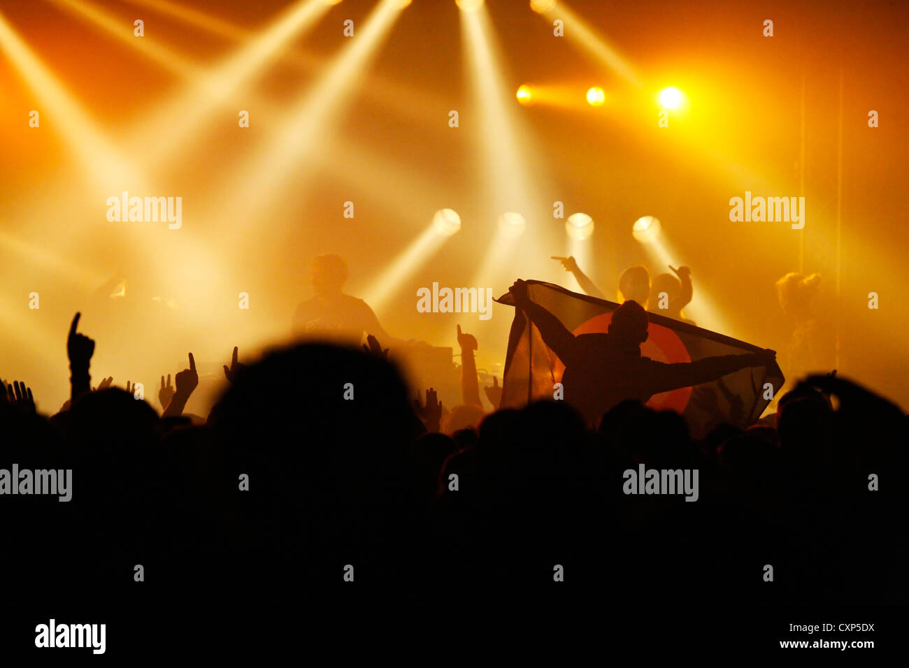 Silhouetted spectators and ambiance during live rock concert with rockers on stage illuminated by spotlights - Stock Image