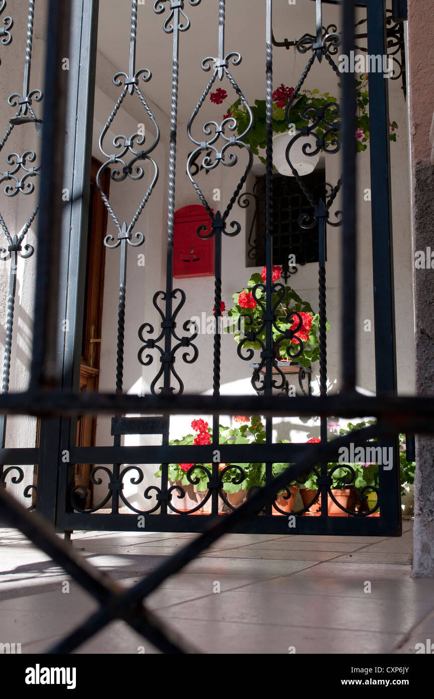 House veranda with cast iron gate and flowers, Bakar, Croatia - Stock Image